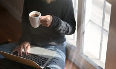 A girl wearing blue jeans and a black sweater, sitting by a window with a cup of coffee and a laptop.