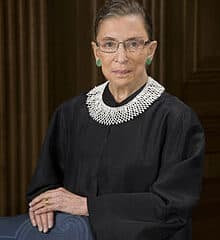 Associate justice of the Supreme Court, Ruth Bader Ginsburg standing with her arms crossed over a blue chair.