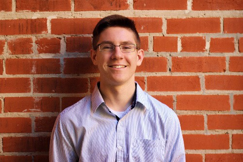 Austin Bauley with short brown hair and glasses, wearing a light purple polo shirt, while standing in front of a brick wall.