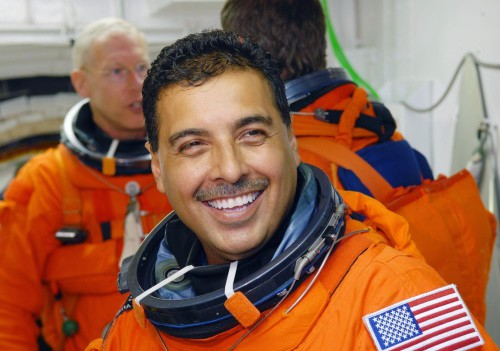 Jose Moreno Hernandez wearing an orange NASA suit with a mustache smiling while standing in front of two other NASA astronauts at the NASA space station.