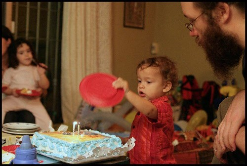 A little boy holding a red plate in his hand, while trying to blow out the candles on his cake, his dad is on the right, and a little dark curly haired girl with a dress is across is on the left.