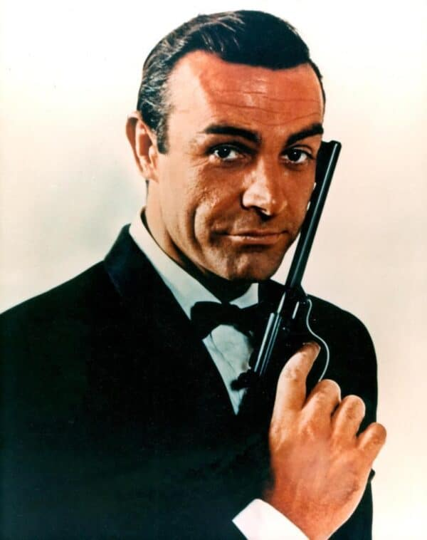 Sean Connery as James Bond in Licence to Kill, holding a gun up to his face and smiling