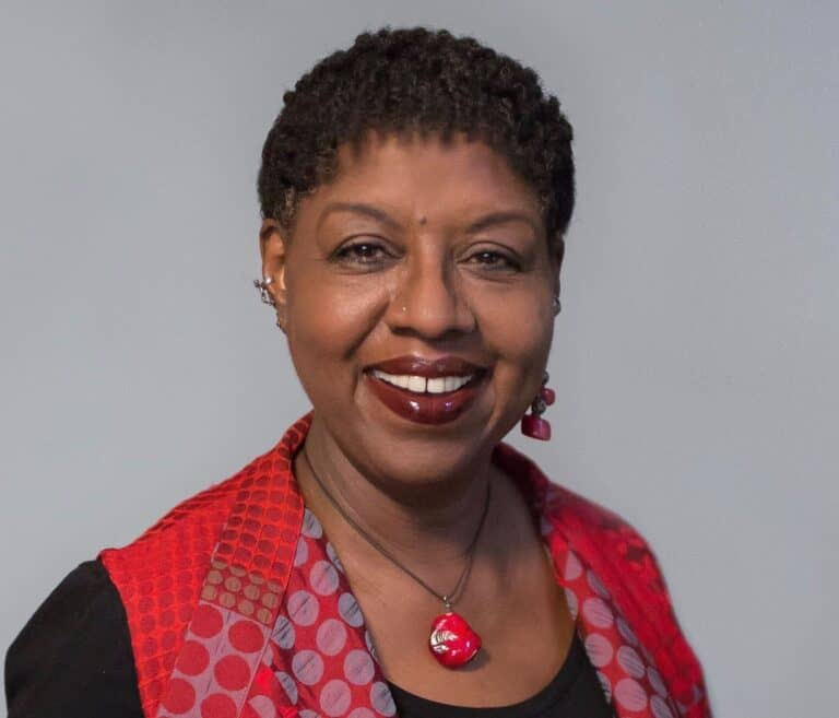 Nikki Grimes, in a red vest and black shirt, looking into the camera and smiling with a grey backdrop behind her.