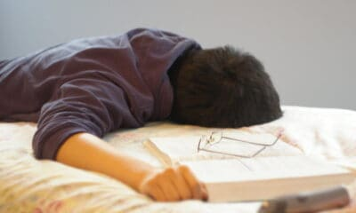 Person laying face down on a bed, sleeping, glasses laying on a book on the bed.
