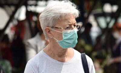 Elderly woman in a white long sleeve shirt, mask, carrying a black purse with her as she walks outside