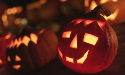 Two halloween jac-o-lanterns smiling and glowing in the dark outside of a house