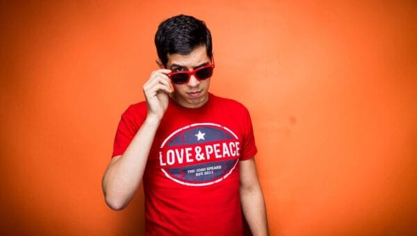 Joshua Rodriguez in a red Love & Peace shirt, red sunglasses, tilted and looking into the camera