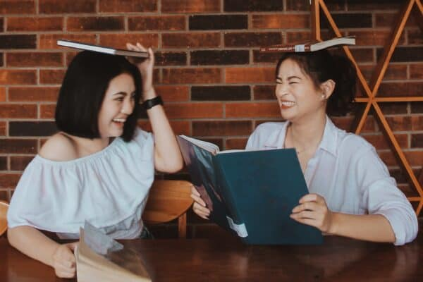 Two college students having a blast balancing books on their heads and reading at a table, laughing and smiling