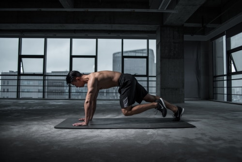 A man with dark spikey hair wearing long dark grey shorts and tennis shoes doing a push up on a grey mat in an empty building.