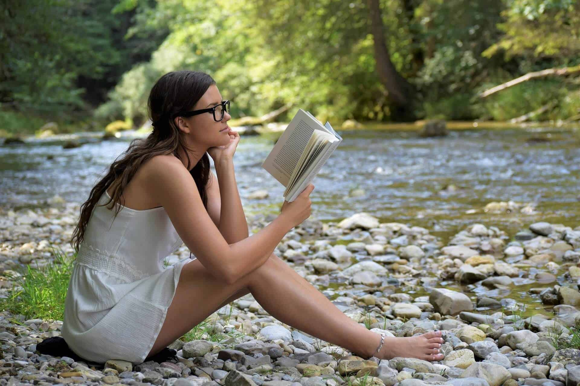 A college girl sitting on the side of a river reading a book