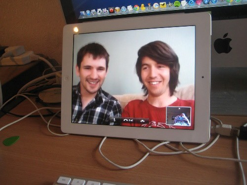A young man with short brown hair and a plaid shirt, and another young man with short black hair watch someone in a video, while celebrating birthdays virtually during COVID 19.