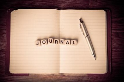 "A small journal with the pages turned, followed by seven little beige letter tiles spelling out the word, ""journal,"" and a grey ballpoint pen."
