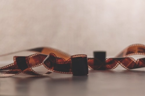 A light brown blurry background with a dark brown film reel tangled on the ground.