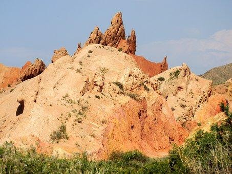 A giant orange mountain with some large pointy orange rocks on a sunny day.
