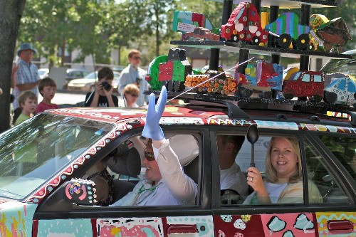 A car decorated with food and birthday items with four people in the car, driving down the street.