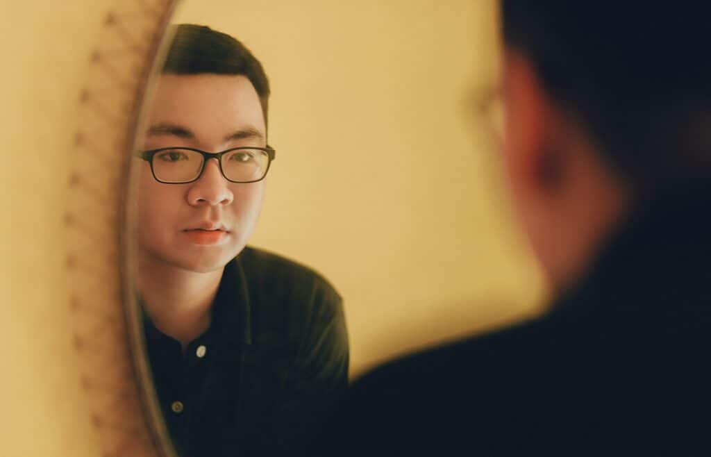 Man in a black shirt and glasses looking at himself in the mirror