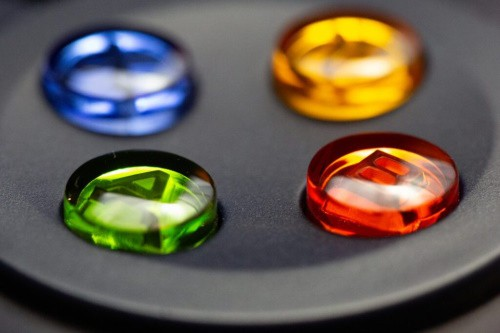 Zoomed in on an Xbox controller, featuring the green A button, red B, yellow Y, and blue X.