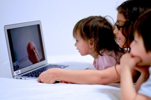 Three children looking at their grandfather online while celebrating a birthday virtually during COVID-19.