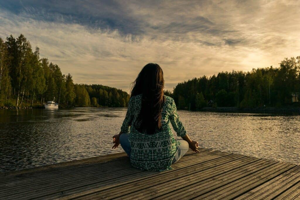A woman in a green and white patterned shirt and pants, sitting on a dock on a body of water, in a yoga pose