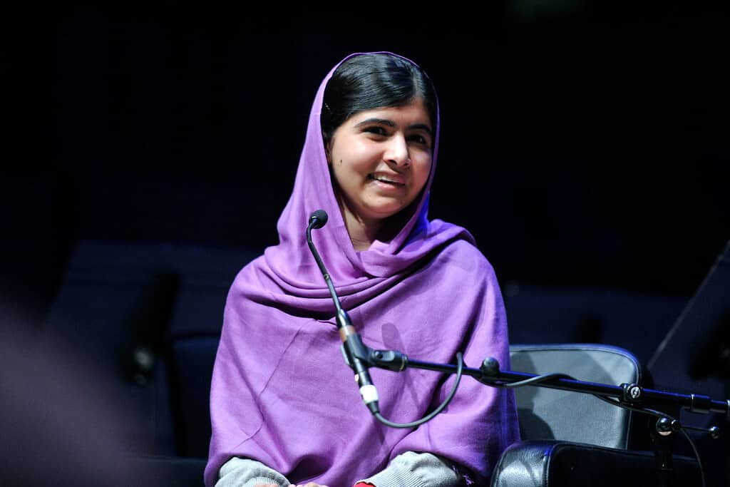 Malala Yousafzai wearing a purple headscarf in front of a microphone.