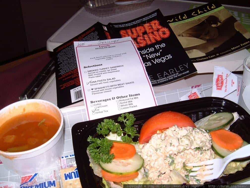 A container of food, soup, and a menu next to some books.