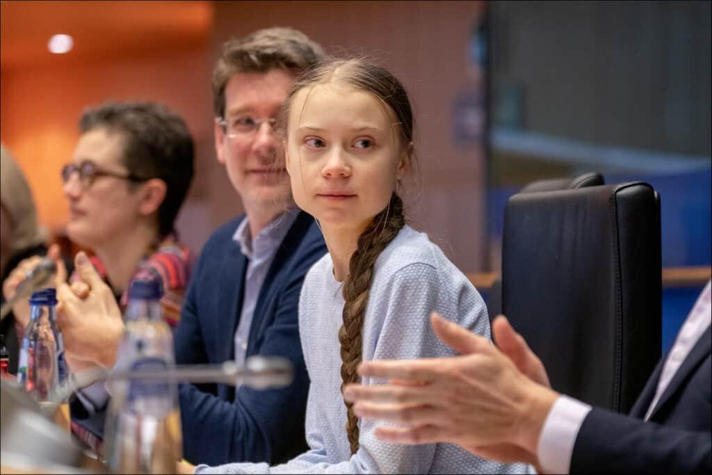 Greta Thunberg sitting at a table.