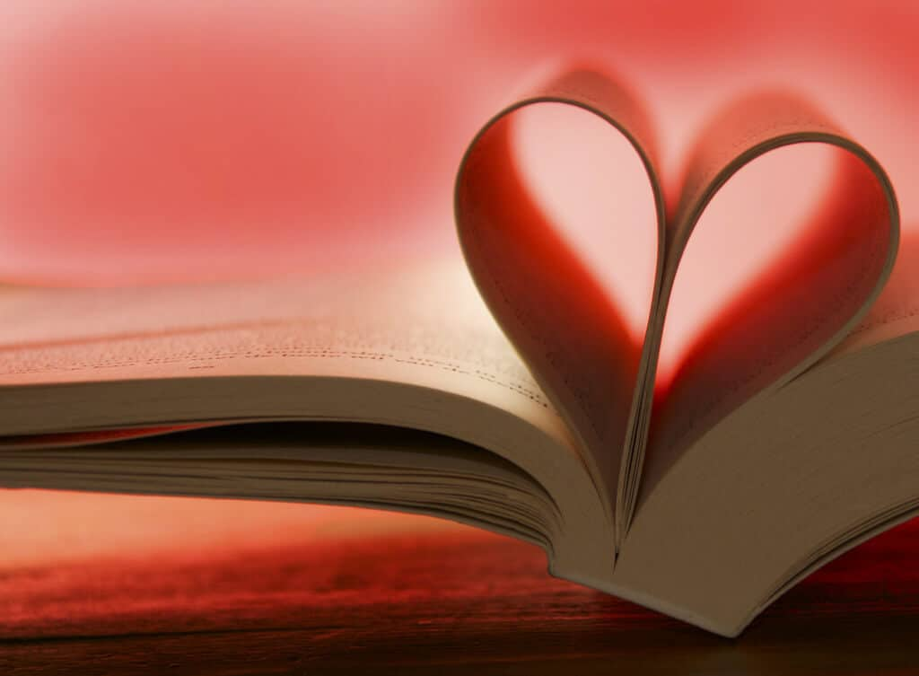 A close up of the side of a book with the pages forming a heart and a red back light.