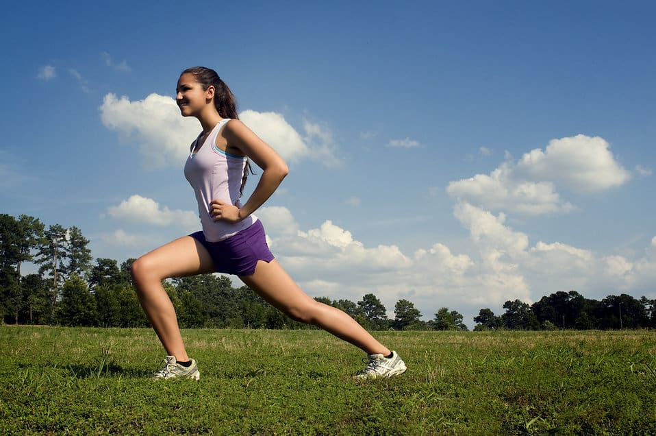 College student doing lunges in a field.