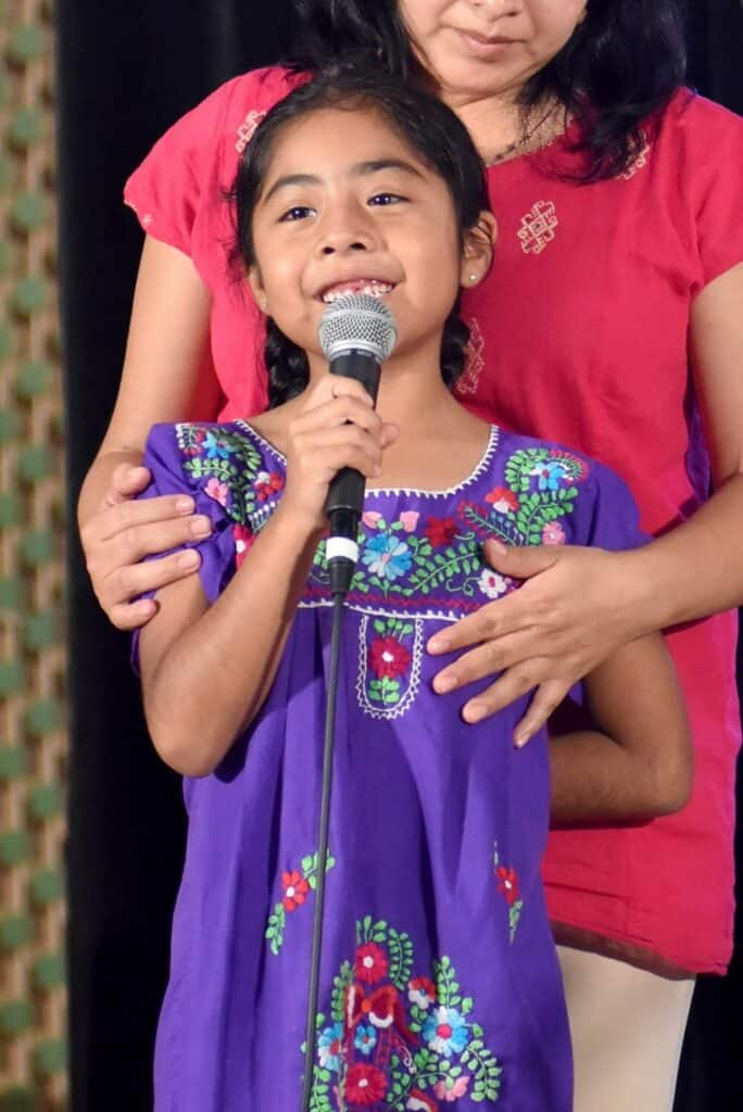 Sophie Cruz wearing a purple dress, smiling and holding a microphone.