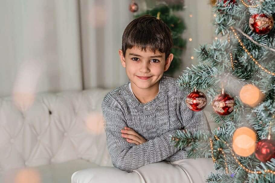 A boy in a grey sweater smiling at the camera with his arms crossed next to a Christmas tree.
