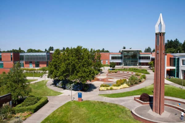 Aerial view of a central quad of a university, showing many trees, a tower, and a building: Hanna Hall