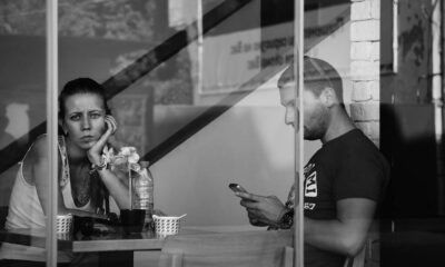 A man and a woman presumably at a coffee shop, the woman looking sad towards the camera behind the window pane, and the man focused on his phone texting