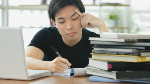 Man in a black shirt, writing on a piece of paper in between a stack of books and his computer