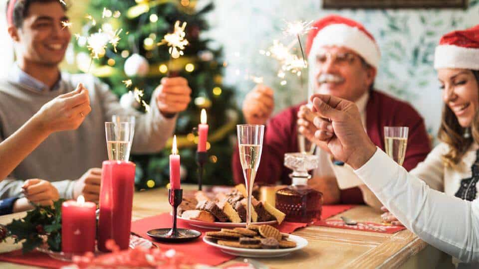 5 people sitting around a table holding sparklers wearing Santa hats during the holidays.