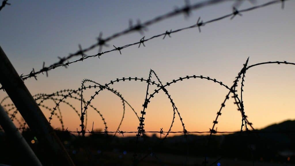 A barbed wire fence as the sun sets in the distance, the mountains out of focus behind.