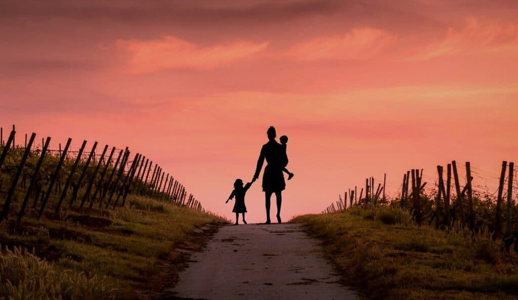 A mother holding her two children as they walk up a hill, fence on either side of them, into the sunset