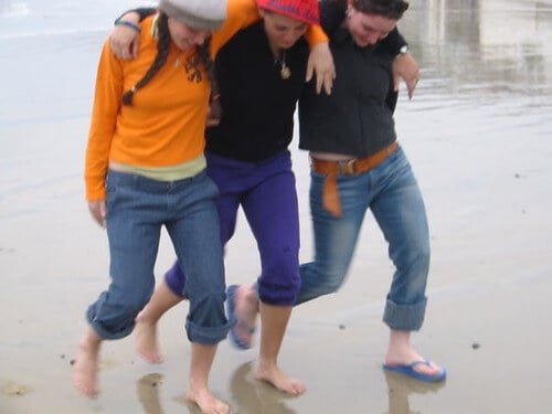 Three people, walking on the beach at the same pace, with their arms wrapped around one another's shoulders and laughing