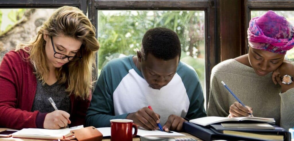Three people sitting at a table, focused on writing in their notebooks, studying