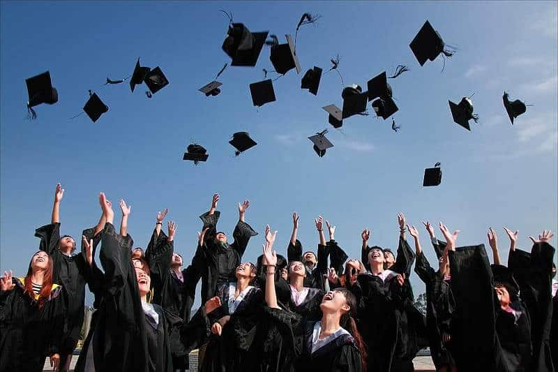 A large group of students celebrating graduation by throwing their caps into the air and smiling