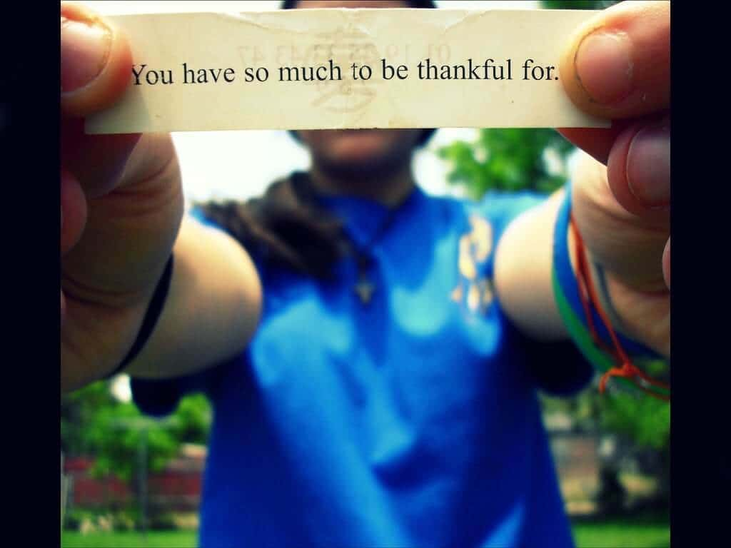 "A person in a blue shirt, standing and holding the fortune from a fortune cookie towards the camera, with the caption ""You have so much to be thankful for."""