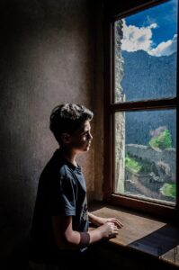 Portrait of a young child looking out a window.
