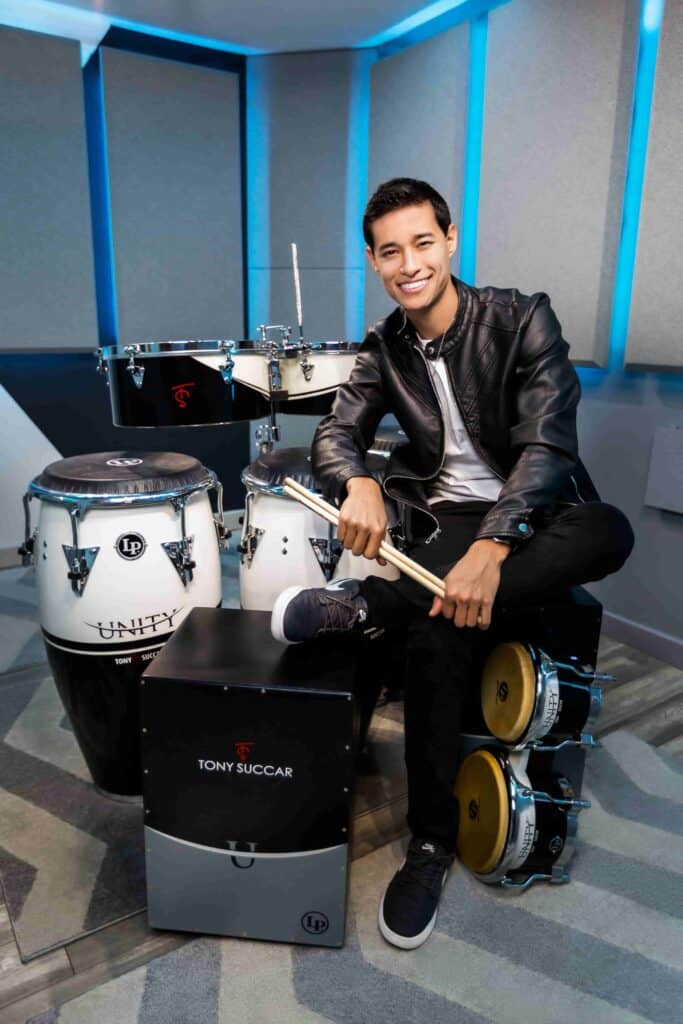 Tony Succar, sitting next to a drum set with one leg crossed over the other, sitting and smiling while looking into the camera