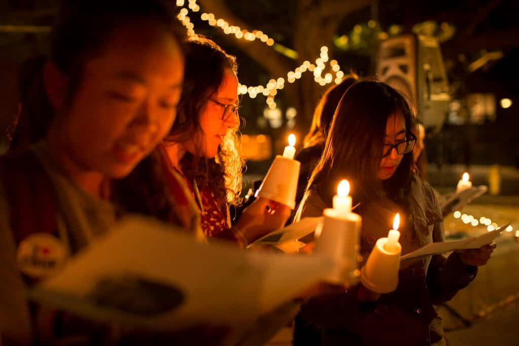 Four girls holding candles, singing Christmas carols.