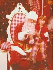Santa Claus sitting with a child on his lap.