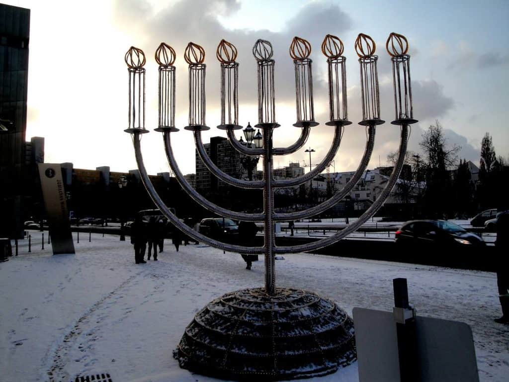 A large sculpture of a menorah outside in the snow.