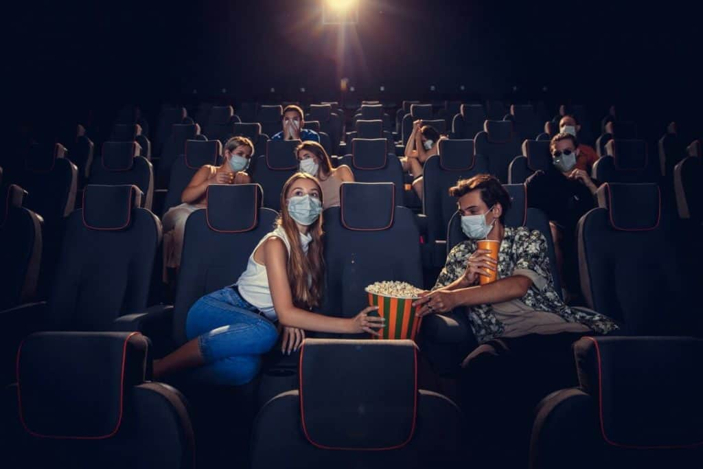 People eating popcorn sitting in a movie theater.