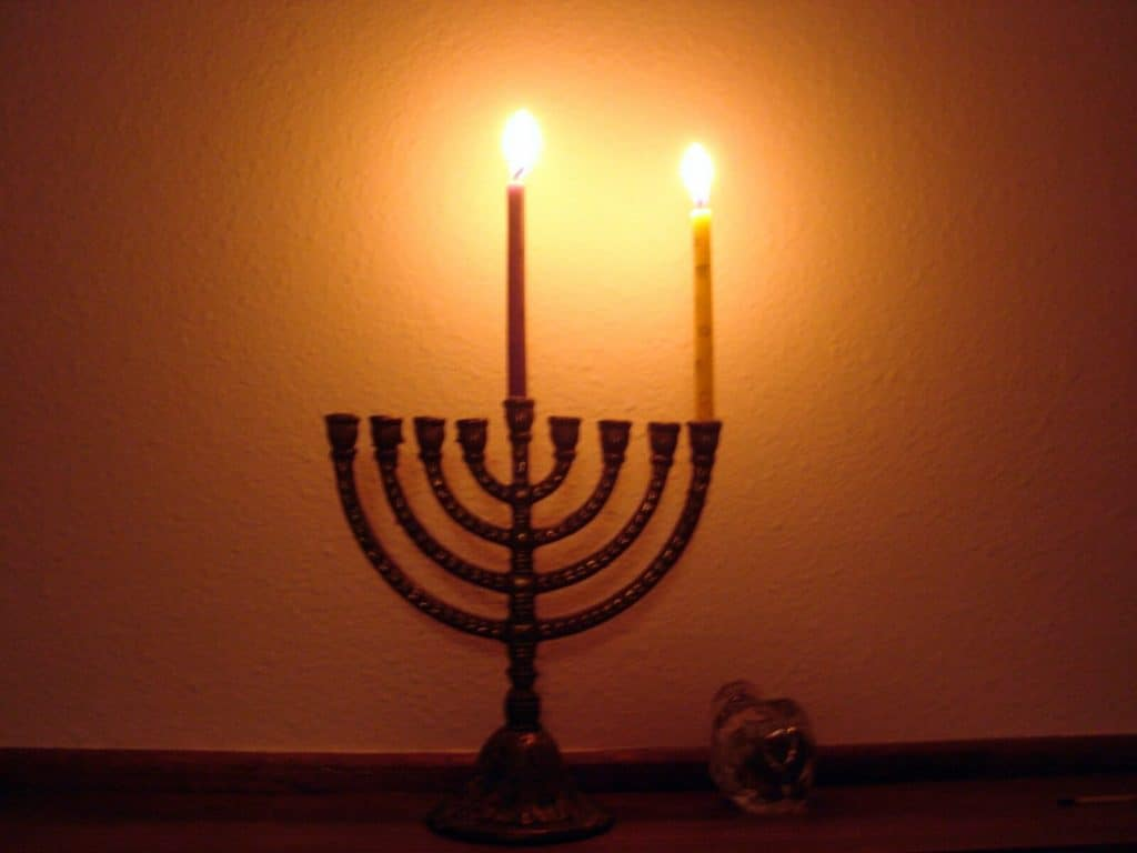 A menorah with two candles burning, one in the middle and one on the far right.
