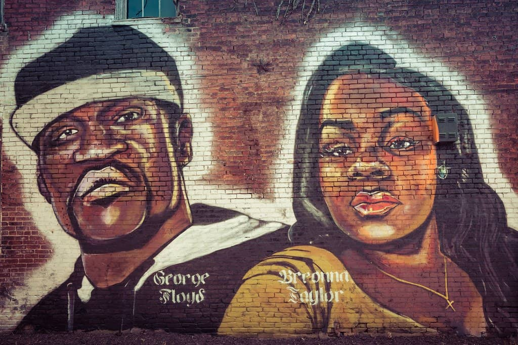 BLM artwork on a brick wall depicting George Floyd and Breonna Taylor.