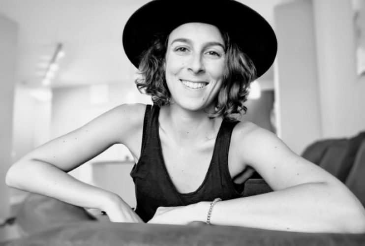A black and white photo of Thais Drassinower wearing black hat and tank top.