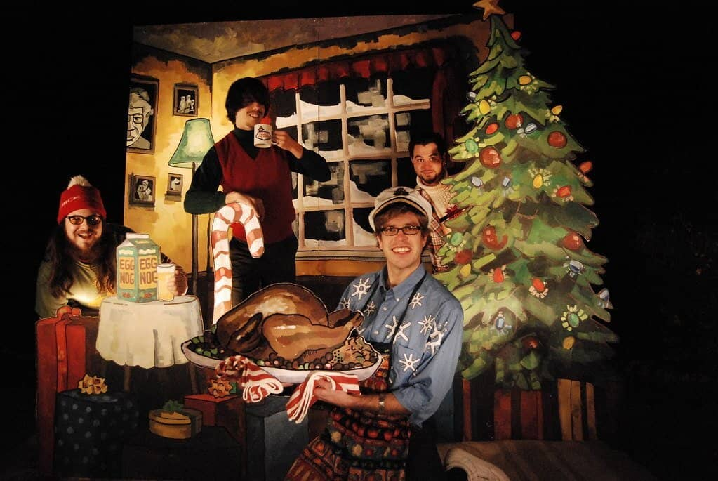 Four men dressed up holding a turkey by a Christmas tree.